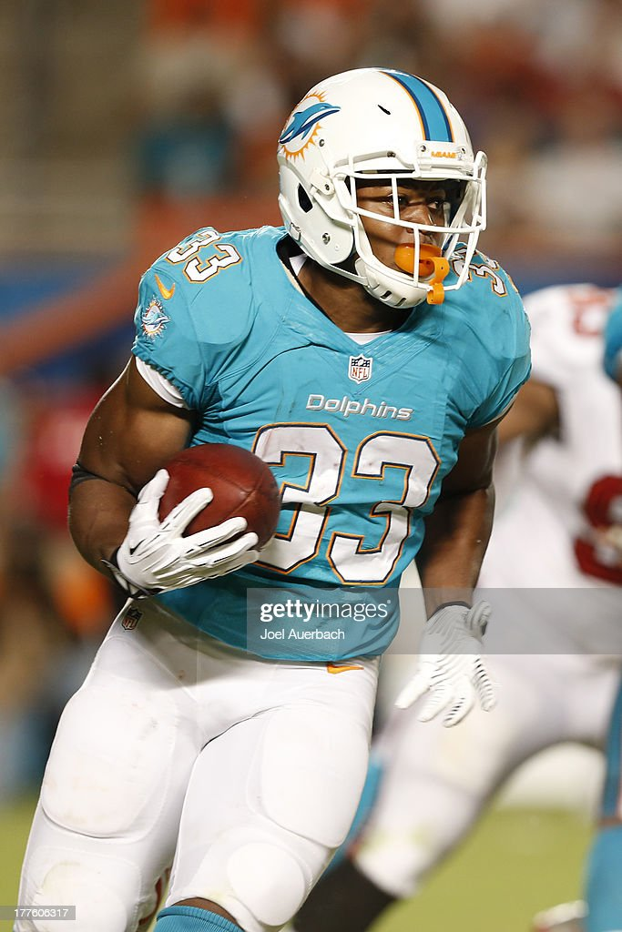 Daniel Thomas #33 of the Miami Dolphins runs with the ball during first half action against the Tampa Bay Buccaneers during a preseason game on August 24, 2013 at Sun Life Stadium in Miami Gardens, Florida.