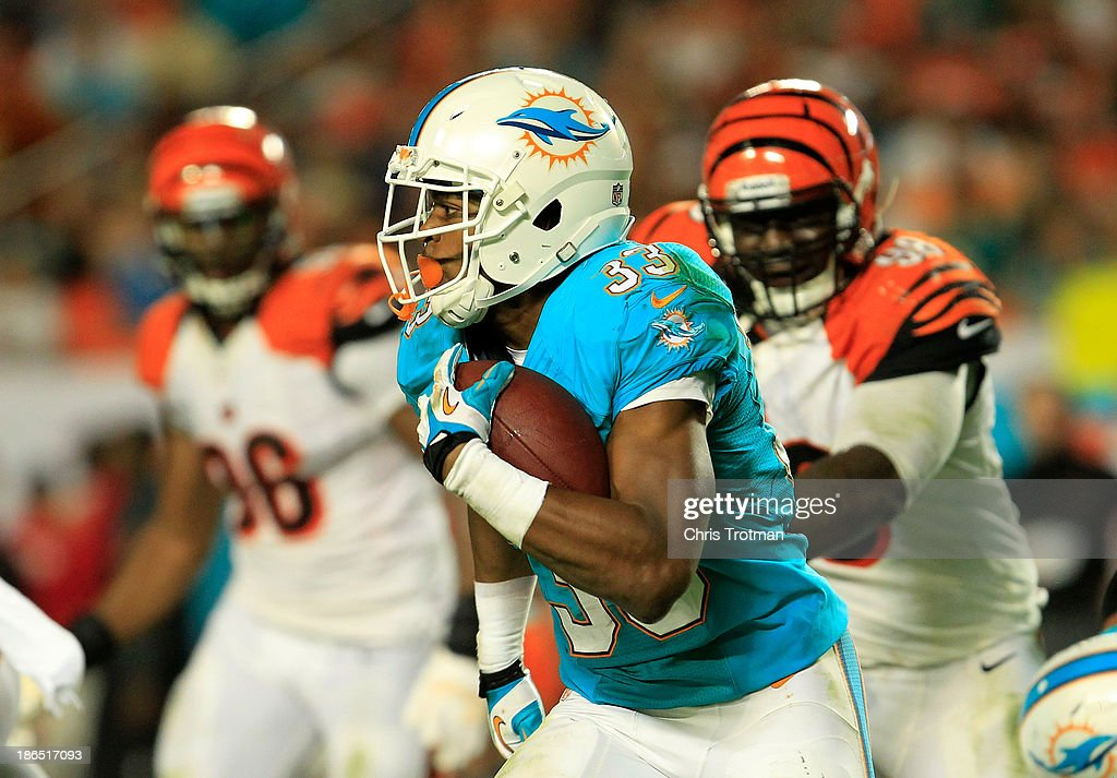 Daniel Thomas #33 of the Miami Dolphins runs with the ball under pressure from (R) Brandon Thompson #98 of the Cincinnati Bengals at Sun Life Stadium on October 31, 2013 in Miami Gardens, Florida.