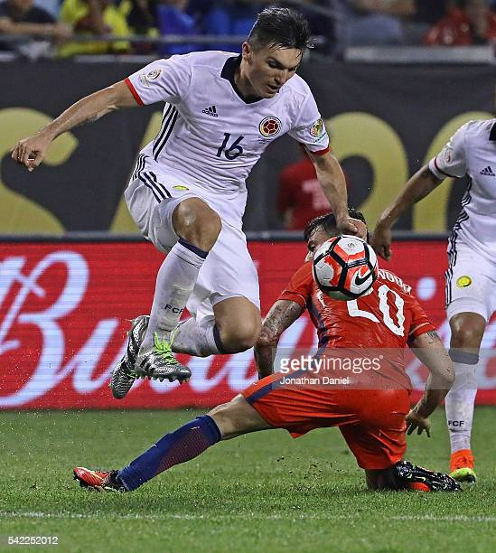 Daniel Torres of Colombia leaps over a tackle attempt by Charles Aranguiz of Chile during a semifinal match in the 2016 Copa America Centernario at...