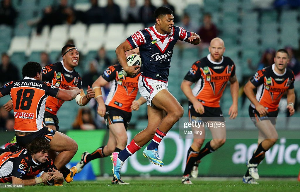 Daniel Tupou of the Roosters breaks a tackle on his way to scoring a try during the round 23 NRL match between the Wests Tigers and the Sydney Roosters at Allianz Stadium on August 19, 2013 in Sydney, Australia.
