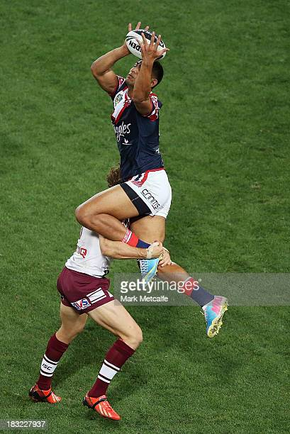 Daniel Tupou of the Roosters takes a high ball over David Williams of the Sea Eagles to score a try during the 2013 NRL Grand Final match between the...