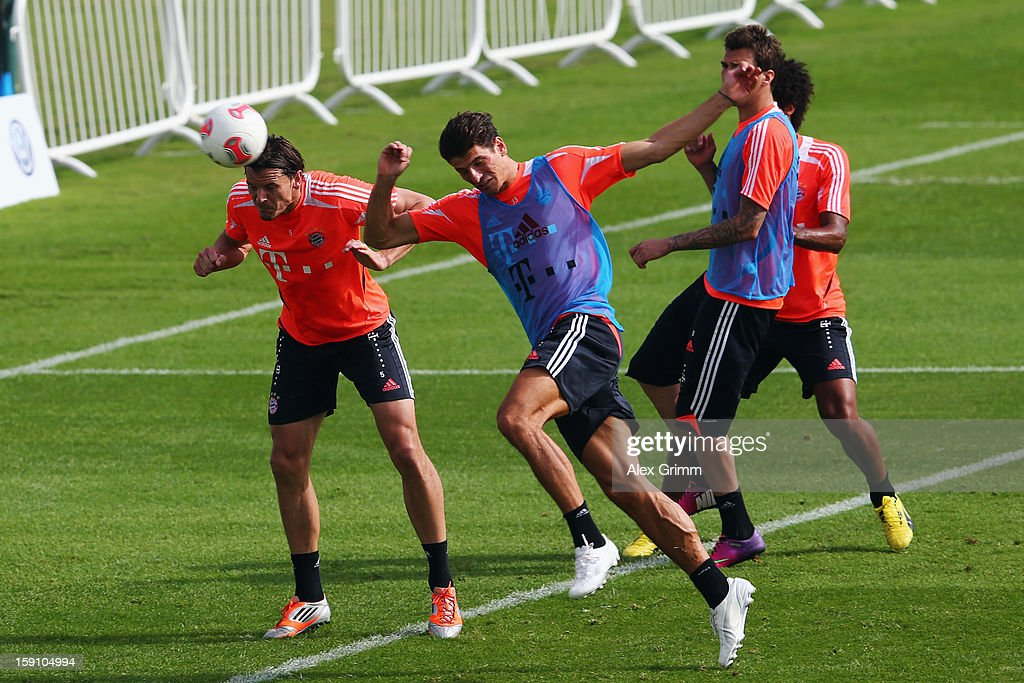 Daniel van Buyten (L) jumps for a header with Mario Gomez during a Bayern Muenchen training session at the ASPIRE Academy for Sports Excellence on January 8, 2013 in Doha, Qatar.