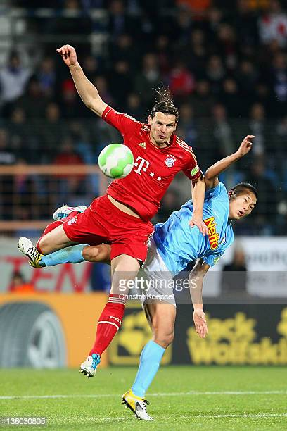 Daniel van Buyten of Bayern and Chong Tese of Bochum go up for a header during the DFB Cup round of sixteen match between VfL Bochum and FC Bayern...