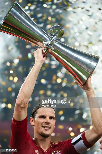 Daniel Van Buyten of Bayern Muenchen holds the trophy after winning a friendly match against VfL Wolfsburg as part of the Audi Football Summit 2012...