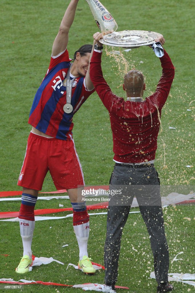 Daniel van Buyten of Bayern Muenchen spoils beer over head coach Josep Guardiola while holding the trophy to celebrate winning the German Championship after the Bundesliga match between FC Bayern Muenchen and VfB Stuttgart at Allianz Arena on May 10, 2014 in Munich, Germany.
