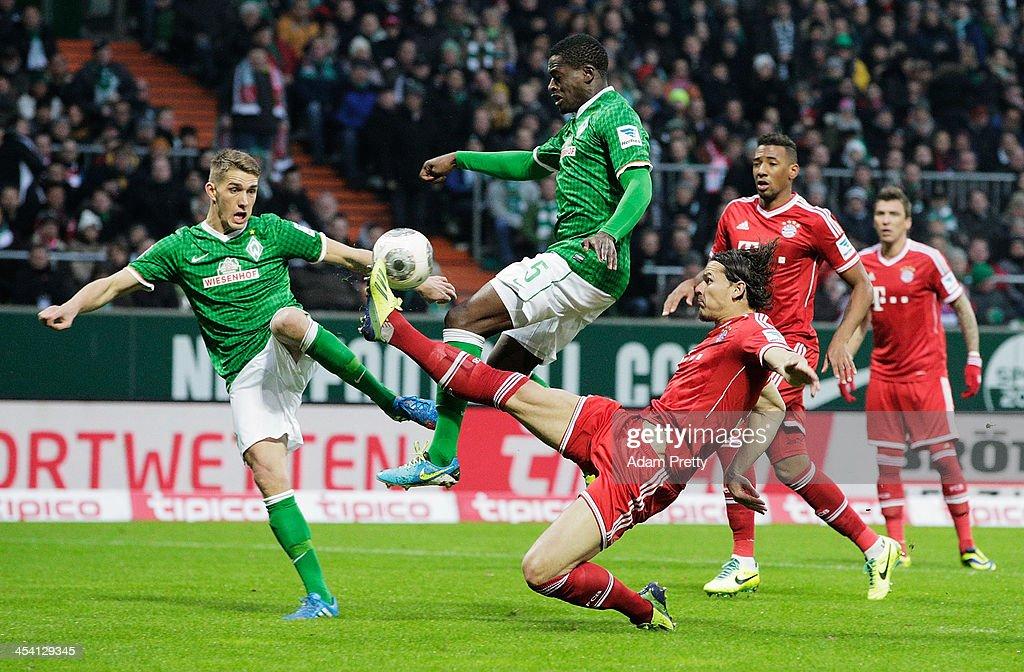 Daniel van Buyten of Bayern saves a goal attempt by Assani Lukimya of Bremen during the Bundesliga match between Werder Bremen and FC Bayern Muenchen at Weserstadion on December 7, 2013 in Bremen, Germany.