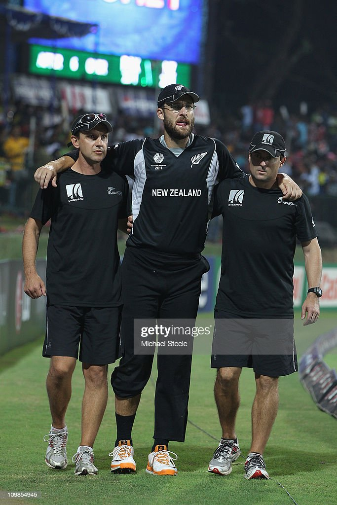 Daniel Vettori the New Zealand captain is helped off the field by team physios after injuring his knee during the New Zealand v Pakistan 2011 ICC...