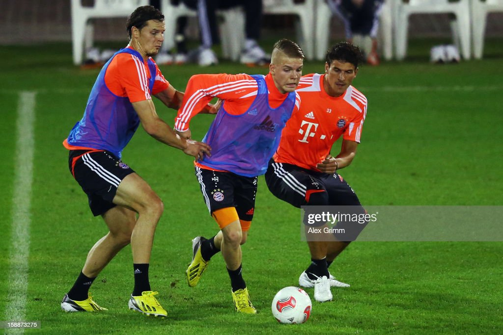 Daniel Wein (C) is challenged by Daniel van Buyten (L) and Mario Gomez during a Bayern Muenchen training session at the ASPIRE Academy for Sports Excellence on January 2, 2013 in Doha, Qatar.