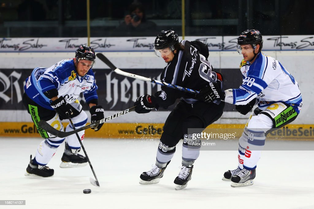 Daniel Weiss (C) of Ice Tigers is challenged by Sebastian Osterloh (L) and Matt Hussey of Straubing during the DEL match between Thomas Sabo Ice Tigers and Straubing Tigers at Arena Nuernberger Versicherung on December 11, 2012 in Nuremberg, Germany.