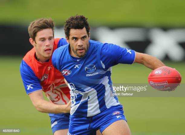 Daniel Wells is tackled by Ryan Bastinac during a North Melbourne Kangaroos AFL training session at Arden Street Ground on August 14 2014 in...