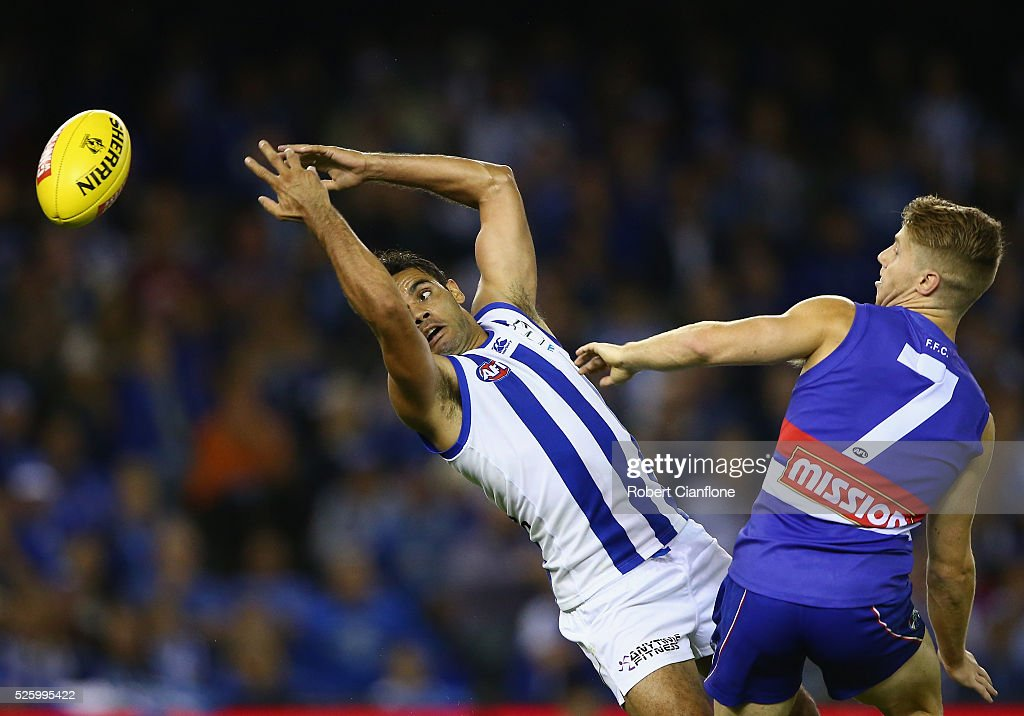 Daniel Wells of the Kangaroos is challenged for the ball by Lachie Hunter of the Bulldogs during the round six AFL match between the North Melbourne Kangaroos and the Western Bulldogs at Etihad Stadium on April 29, 2016 in Melbourne, Australia.