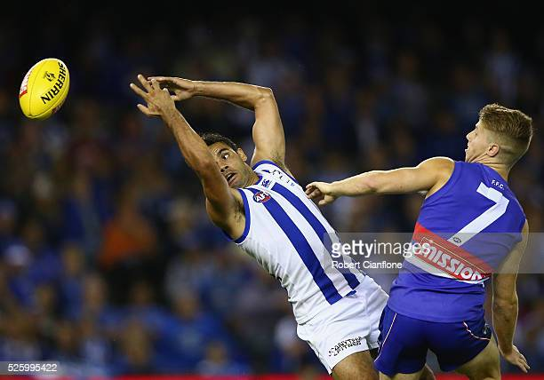 Daniel Wells of the Kangaroos is challenged for the ball by Lachie Hunter of the Bulldogs during the round six AFL match between the North Melbourne...