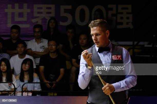Daniel Wells of Wales chalks the cue during his first round match against Judd Trump of England on day two of Evergrande 2017 World Snooker China...