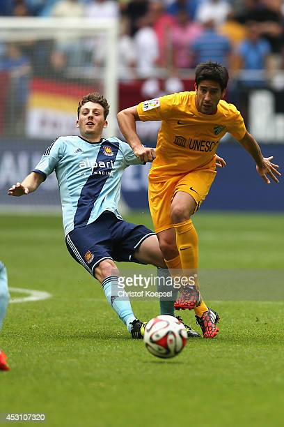 Daniel Whitehead of West Ham United challenges Pablo Perez of Malaga during the match between FC Malaga and West Ham United as part of the Schalke 04...