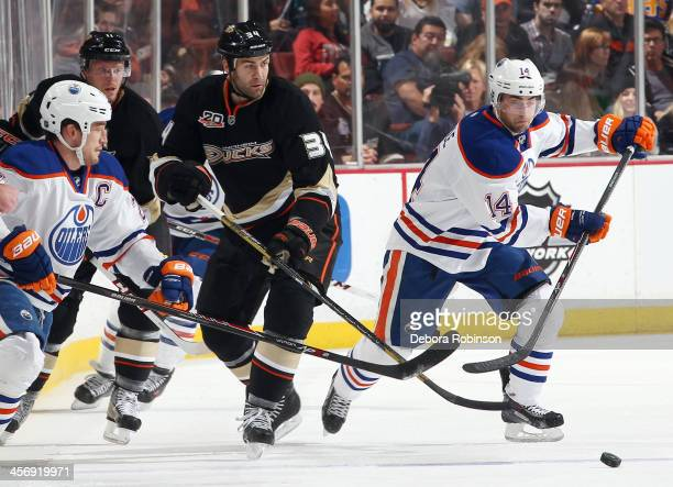 Daniel Winnik of the Anaheim Ducks battles for the puck against Jordan Eberle of the Edmonton Oilers on December 15 2013 at Honda Center in Anaheim...