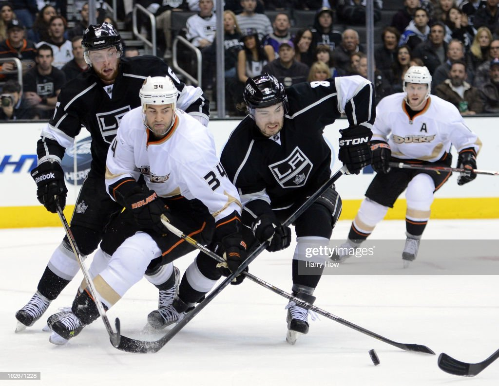 Daniel Winnik #34 of the Anaheim Ducks goes after the puck with Drew Doughty #8 and Jake Muzzin #6 of the Los Angeles Kings during the first period at Staples Center on February 25, 2013 in Los Angeles, California.