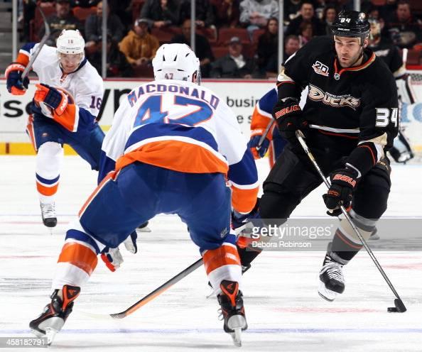 Daniel Winnik of the Anaheim Ducks handles the puck against Andrew MacDonald of the New York Islanders on December 9 2013 at Honda Center in Anaheim...