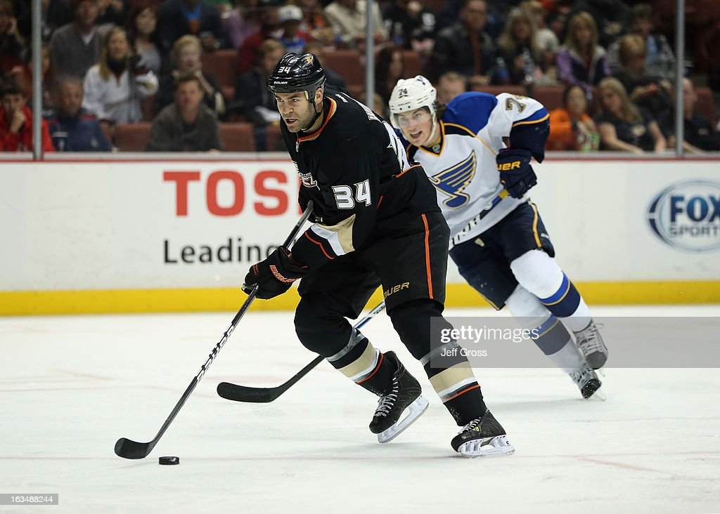 <a gi-track='captionPersonalityLinkClicked' href=/galleries/search?phrase=Daniel+Winnik&family=editorial&specificpeople=2529214 ng-click='$event.stopPropagation()'>Daniel Winnik</a> #34 of the Anaheim Ducks is pursued by <a gi-track='captionPersonalityLinkClicked' href=/galleries/search?phrase=T.J.+Oshie&family=editorial&specificpeople=700383 ng-click='$event.stopPropagation()'>T.J. Oshie</a> #74 of the St. Louis Blues for the puck in the first period at Honda Center on March 10, 2013 in Anaheim, California. The Ducks defeated the Blues 4-2.