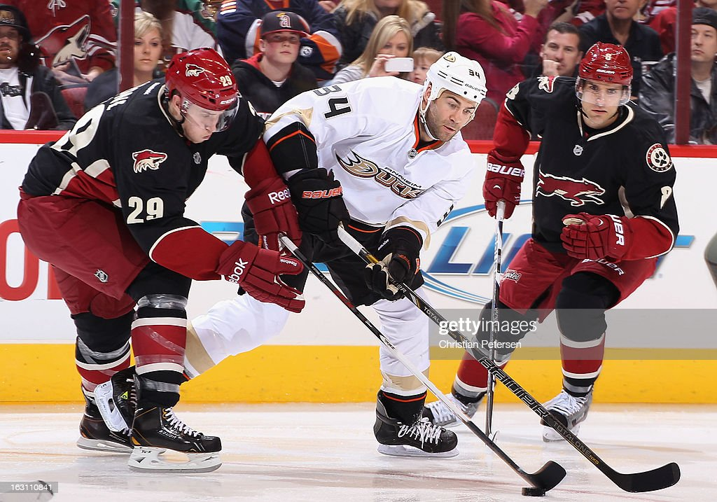 Daniel Winnik #34 of the Anaheim Ducks skates with the puck past Michael Stone #29 and Matthew Lombardi #8 of the Phoenix Coyotes during the second period of the NHL game at Jobing.com Arena on March 4, 2013 in Glendale, Arizona.