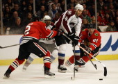 Daniel Winnik of the Colorado Avalanche hops between Duncan Keith and Tomas Kopecky of the Chicago Blackhawks to control the puck at the United...