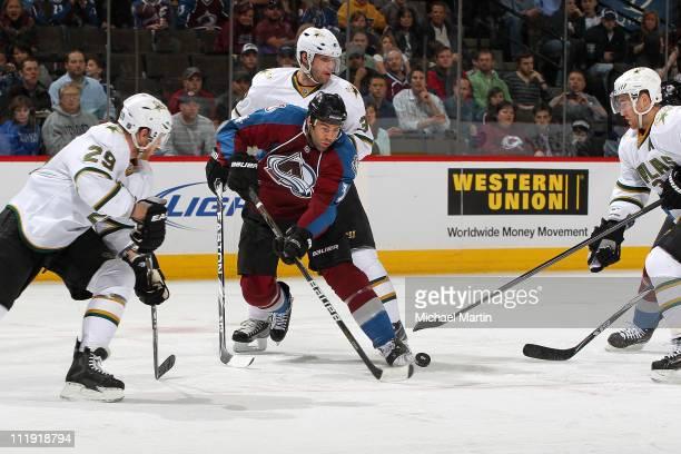 Daniel Winnik of the Colorado Avalanche skates the puck between the defense of Steve Ott Stephane Robidas and Karlis Skrastins of the Dallas Stars in...