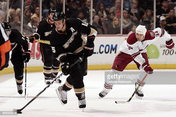 Daniel Winnik of the Phoenix Coyotes races for the puck from behind as Ryan Getzlaf of the Anaheim Ducks controls the puck during the game on...