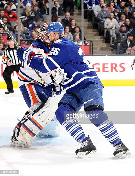 Daniel Winnik of the Toronto Maple Leafs battles for space with Viktor Fasth of the Edmonton Oilers during NHL game action February 7 2015 at the Air...