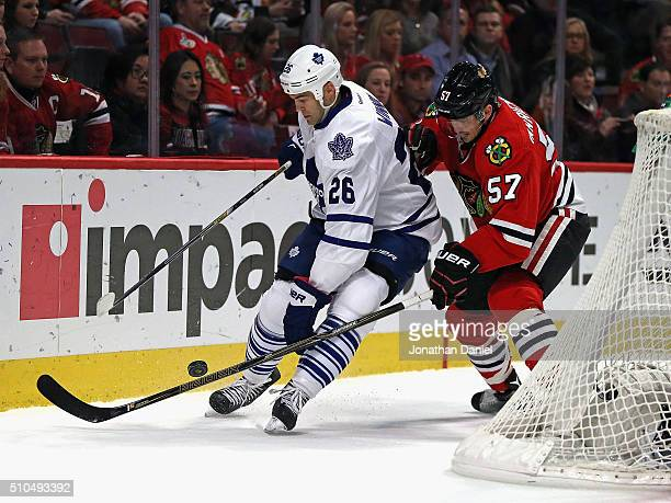 Daniel Winnik of the Toronto Maple Leafs battles for the puck with Trevor van Riemsdyk of the Chicago Blackhawks at the United Center on February 15...