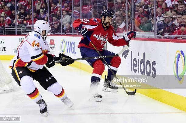 Daniel Winnik of the Washington Capitals controls the puck against Matt Bartkowski of the Calgary Flames in the third period during an NHL game at...
