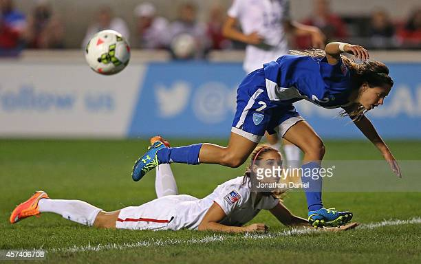 Daniela Andrade of Guatemala jumps over Alex Morgan of the United States after blocking a shot during the 2014 CONCACAF Women's Championship at...