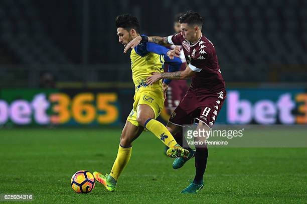 Daniele Baselli of FC Torino competes with Lucas Nahuel Castro of AC ChievoVerona during the Serie A match between FC Torino and AC ChievoVerona at...