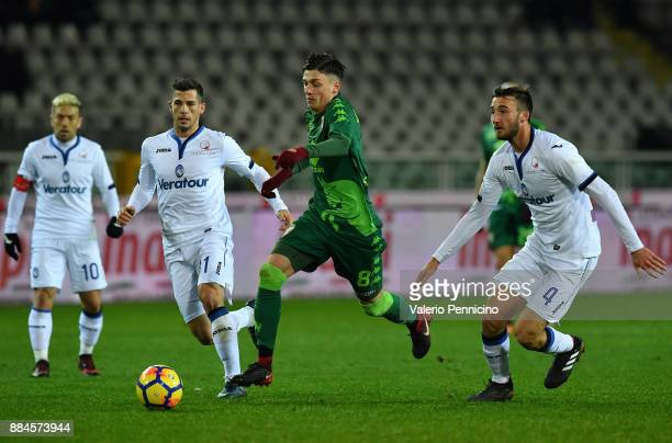 Daniele Baselli of Torino FC in action against Remo Freuler and Bryan Cristante of Atalanta BC during the Serie A match between Torino FC and...
