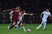 Daniele Baselli of Torino FC is challenged by Mario Suarez of ACF Fiorentina during the Serie A match between Torino FC and ACF Fiorentina at Stadio...
