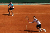 Daniele Bracciali of Italy hits a forehand next to team mate Potito Starace of Italy during the men's doubles round three match between Stephen Huss...