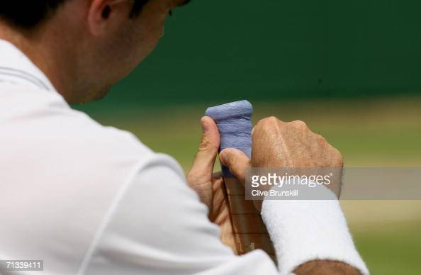 Daniele Bracciali of Italy makes repairs to his racquet between games against Jonas Bjorkman of Sweden during day five of the Wimbledon Lawn Tennis...