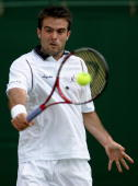Daniele Bracciali of Italy returns a backhand to Stefano Galvani of Italy during day four of the Wimbledon Lawn Tennis Championships at the All...