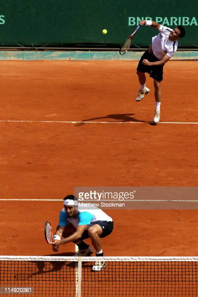 Daniele Bracciali of Italy serves next to team mate Potito Starace of Italy during the men's doubles round three match between Stephen Huss and...