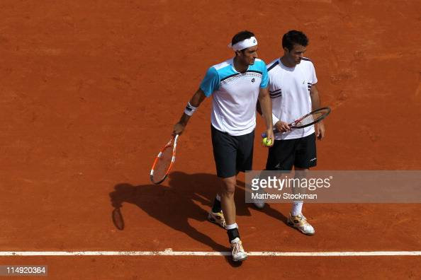 Daniele Bracciali of Italy talks tactics with team mate Potito Starace of Italy during the men's doubles round three match between Stephen Huss and...