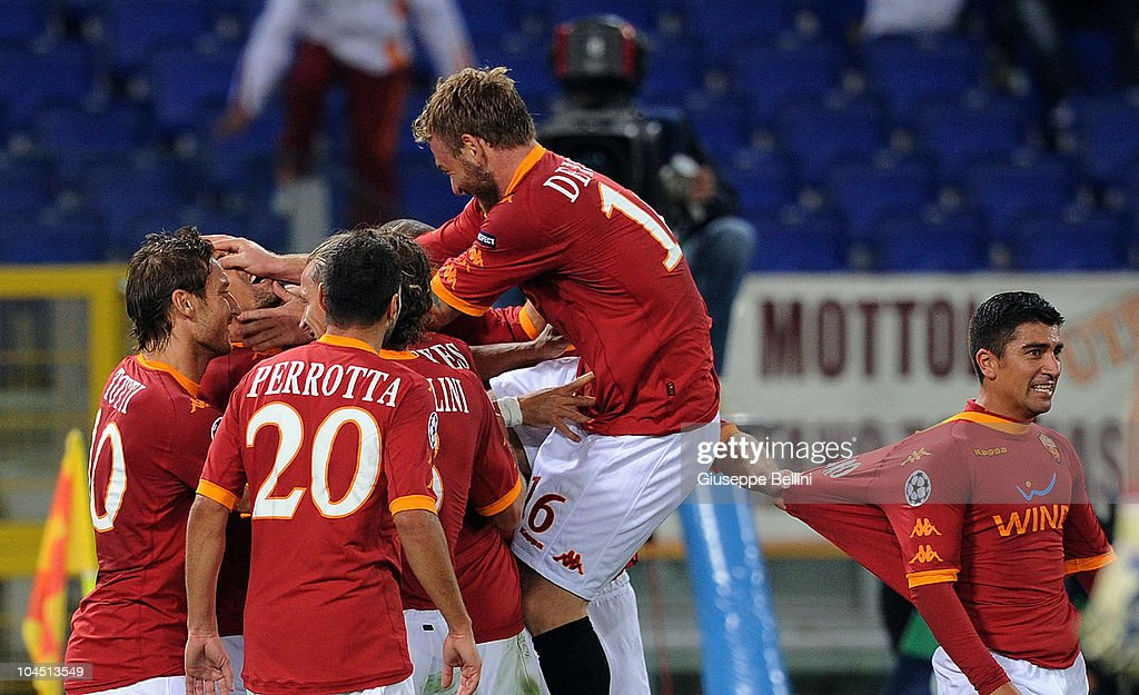 <a gi-track='captionPersonalityLinkClicked' href=/galleries/search?phrase=Daniele+De+Rossi&family=editorial&specificpeople=233652 ng-click='$event.stopPropagation()'>Daniele De Rossi</a> (top) and AS Roma team-mates celebrate Marco Borriello's 2-0 goal during the UEFA Champions League group E match between AS Roma and CFR Cluj at Stadio Olimpico on September 28, 2010 in Rome, Italy.