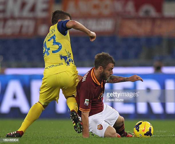 Daniele De Rossi of AS Roma competes for the ball with Alberto Paloschi of AC Chievo Verona during the Serie A match between AS Roma and AC Chievo...
