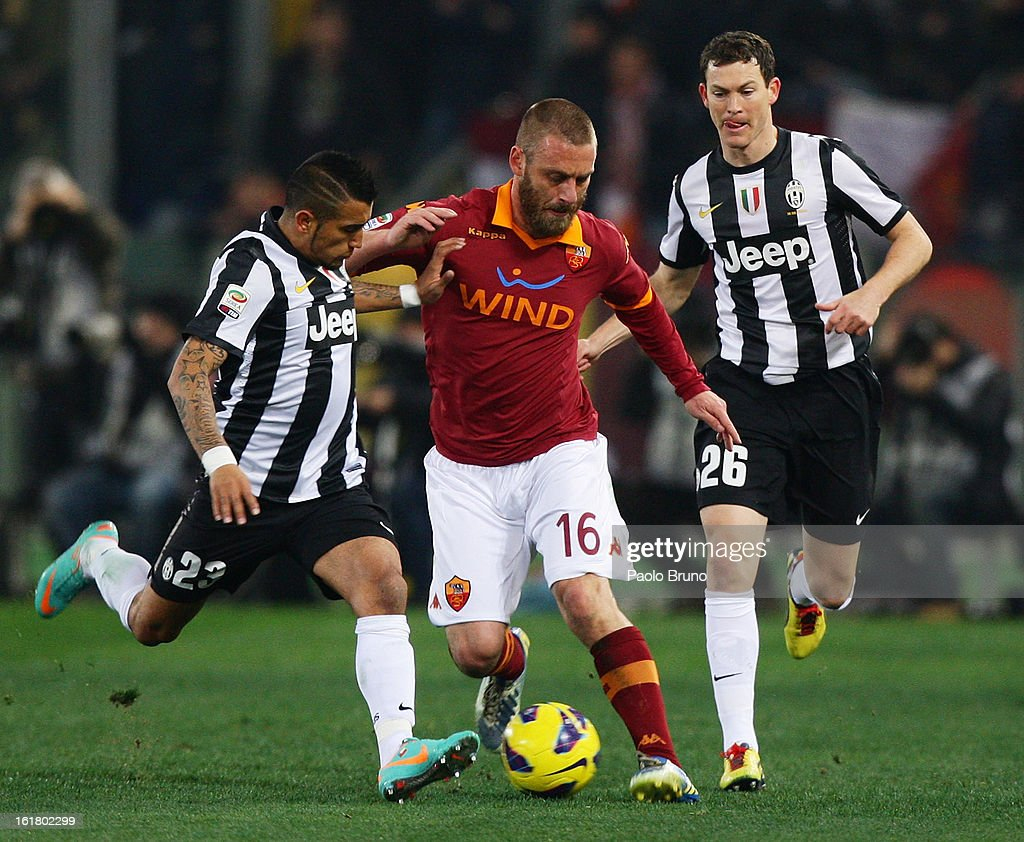 <a gi-track='captionPersonalityLinkClicked' href=/galleries/search?phrase=Daniele+De+Rossi&family=editorial&specificpeople=233652 ng-click='$event.stopPropagation()'>Daniele De Rossi</a> (C) of AS Roma competes for the ball with <a gi-track='captionPersonalityLinkClicked' href=/galleries/search?phrase=Arturo+Vidal&family=editorial&specificpeople=2223374 ng-click='$event.stopPropagation()'>Arturo Vidal</a> (L) and <a gi-track='captionPersonalityLinkClicked' href=/galleries/search?phrase=Stephan+Lichtsteiner&family=editorial&specificpeople=709876 ng-click='$event.stopPropagation()'>Stephan Lichtsteiner</a> of Juventus FC during the Serie A match between AS Roma and Juventus FC at Stadio Olimpico on February 16, 2013 in Rome, Italy.