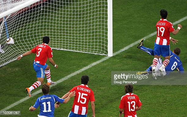 Daniele De Rossi of Italy slides in to score his team's first goal as Claudio Morel and Lucas Barrios of Paraguay look on during the 2010 FIFA World...