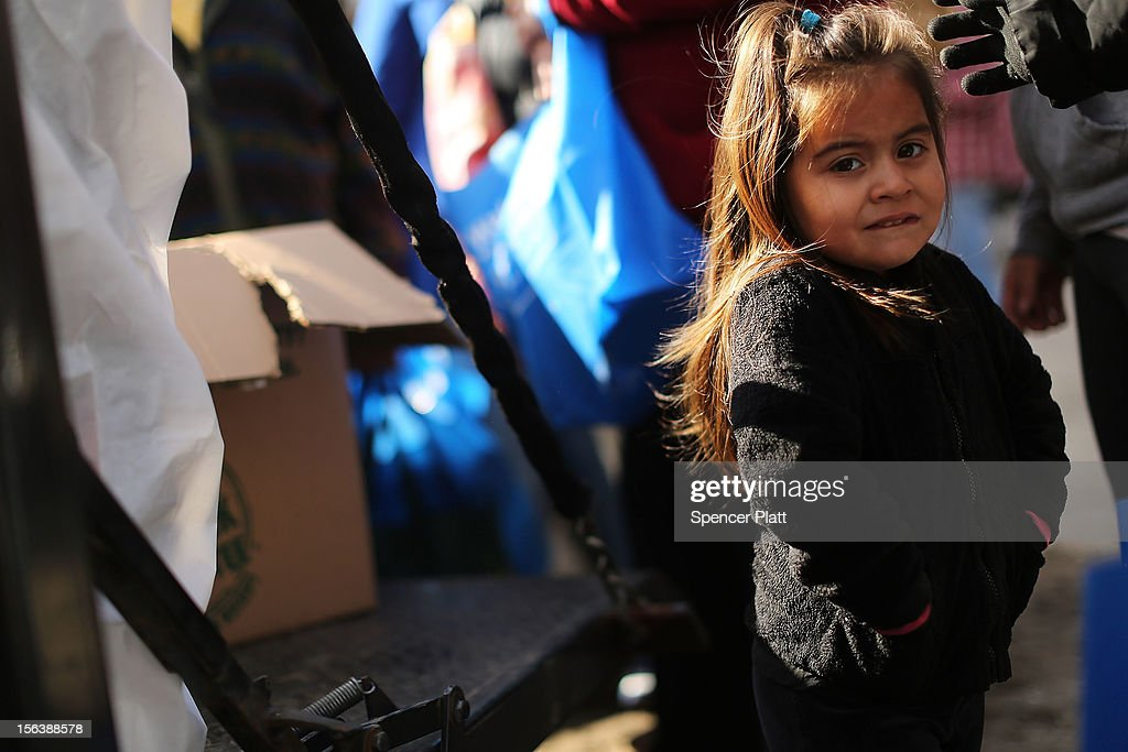 Daniella Rodas, 3, waits in line with her mother for donated items including food and towels from a group called Dream Center in the heavily damaged Rockaway neighborhood where a large section of the iconic boardwalk was washed away on November 14, 2012 in the Queens borough of New York City. Two weeks after Superstorm Sandy slammed into parts of New York and New Jersey, thousands are still without power and heat.