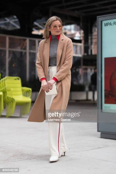 Danielle Bernstein is seen attending Tory Burch during New York Fashion Week wearing a camel wool coat with grey sweater and white with red stripe...