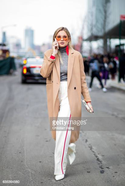 Danielle Bernstein wearing a beige coat jogger pants outside Tory Burch on February 14 2017 in New York City