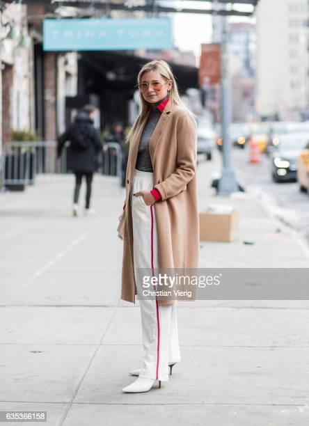 Danielle Bernstein wearing a beige coat white pants outside Tory Burch on February 14 2017 in New York City