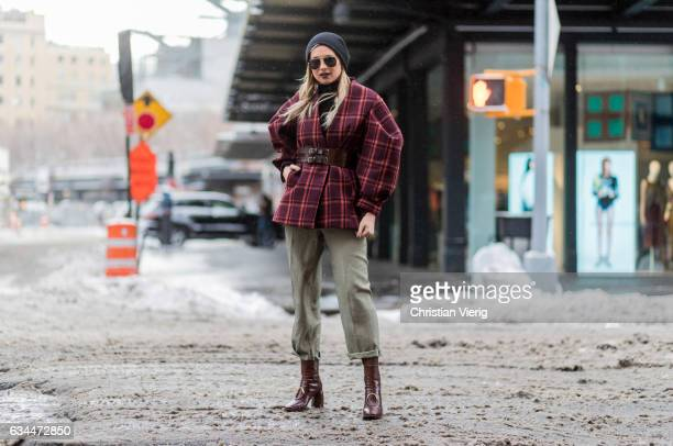 Danielle Bernstein wearing cropped olive pants boots checked red jacket sunglasses beanie outside Creatures of Comfort on February 9 2017 in New York...