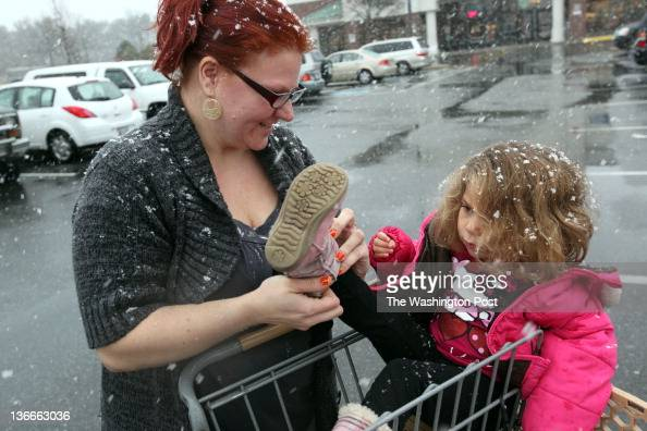 Danielle Greeffield puts boots on her daughter Danna Jordan January 9 2012 in Waldorf Md as the snow falls They were buying groceries