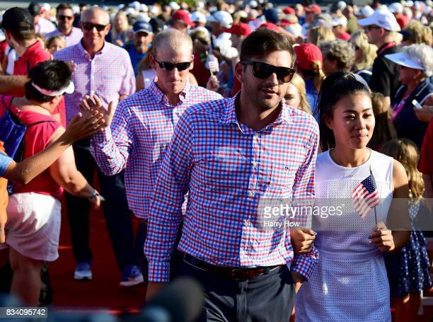 Danielle Kang of Team USA and her caddie Cole Pensanti during opening ceremony for the Solheim Cup at the Des Moines Golf and Country Club on August...