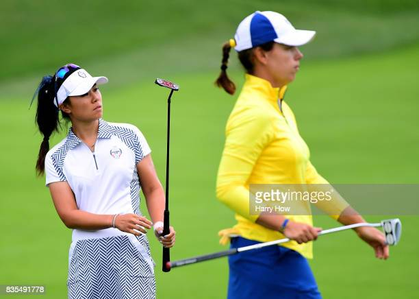 Danielle Kang of Team USA reacts to her putt on the third green behind Karine Icher of Team Europe during the morning foursomes matches of the...